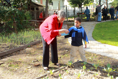 Senator Ruth Hassell-Thompson checks out plants with her grandson